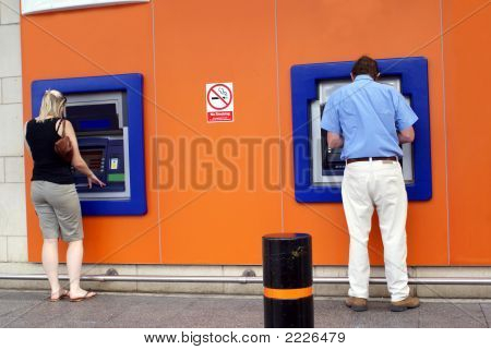 People Using Atm. Man & Woman Using Cash Machines