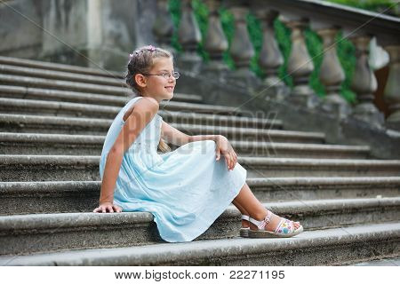 beautiful girl sits on on the stairs in a park