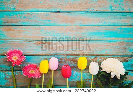 poster of Colorful flowers on vintage wooden background, top view and border design. vintage color tone - flower of spring or summer background
