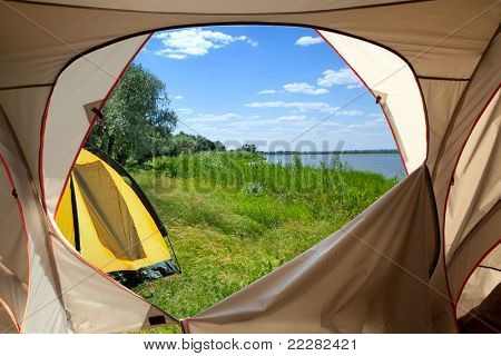 View looking out of door of sun-filled tent upon great outdoors