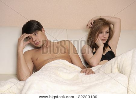 Upset pair of lovers lying on the bed. Family conflict.