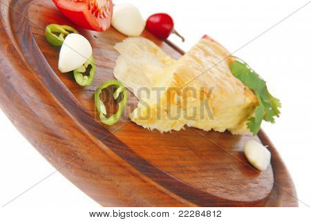 dairy food : vegetable cheese casserole slice on wooden plate served prepared with tomatoes  and garlic isolated over white background