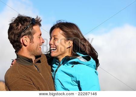 Happy young couple smiling outdoors looking at each other with love. Active young couple portrait during hiking holidays. Asian female model and Caucasian man model.