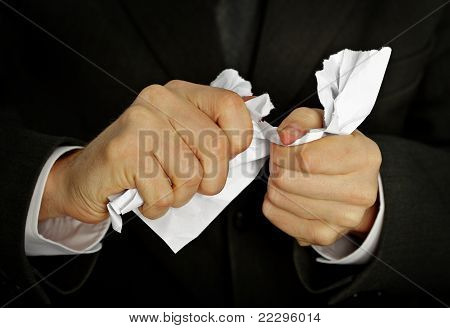 Businessman Hands Furiously Tormenting Document
