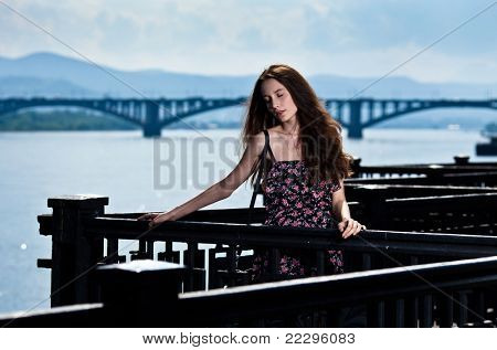Portrait of the beautiful woman with bridge city background