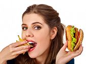 Woman eating french fries and hamburger. Portrait of student consume fast food on table. Victory ove poster