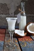 Coconut Milk In Bottle With Broken Coco On Wooden Background. Delicious Milk Cocktail. Copy Space poster