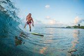 Surfer rides the wave during sunrise surf session. Maldives poster