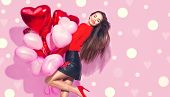 Valentine Beauty girl with red and pink air balloons laughing, on pink polka dots background. Beauti poster