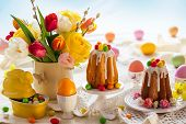 Easter table setting with spring flowers, cakes and easter eggs. poster