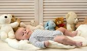 Infant With Blue Eyes And Peaceful Smile Among Teddy Bears poster