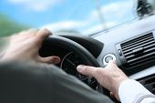 picture of driving school  - Over shoulder view of a man driving a car with his hands on the steering wheel turning quick - JPG