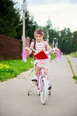 picture of bagpack  - Young school girl with bagpack rides her pink bike to school - JPG