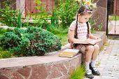 stock photo of bagpack  - Young school girl with pink bagpack sits reading the book - JPG