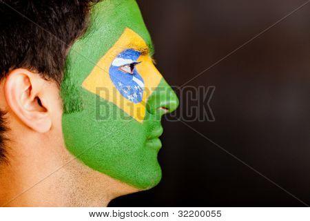 Profilansicht eines brasilianischen Mannes mit Flagge auf seinem Gesicht gemalt