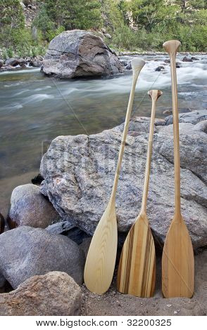 three wooden canoe paddles on shore of mountain river - Cache la Poudre RIver near Fort Collins, Colorado