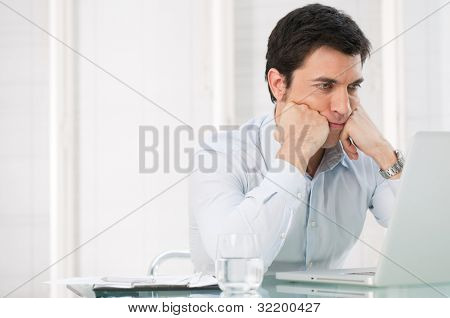 Worried pensive business man watching at his laptop at office