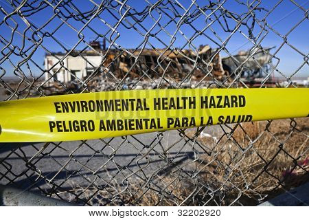 Environmental Health Hazard warning tape on a chain link fence.