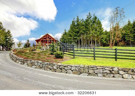 Log Cabin House On The Hill With Road And Fence.