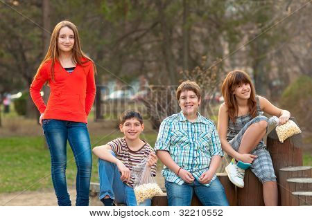 Happy teenage boys and girls spending time together in the park on beautiful spring day
