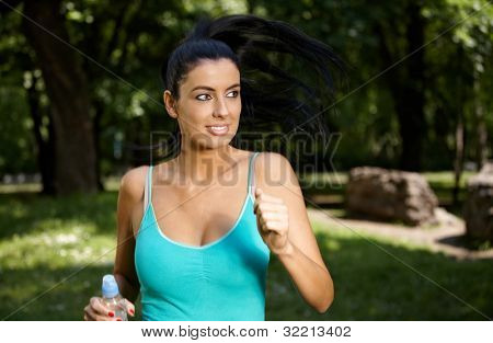 Attractive young woman training in citypark.