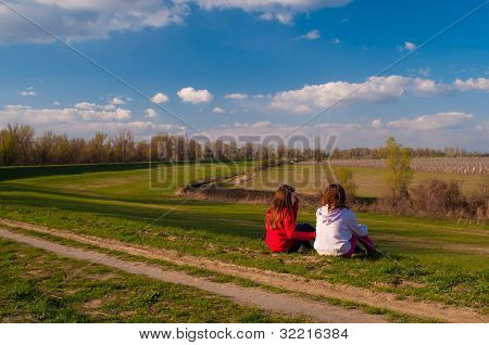Two teenage girls sitting in the grass and talking on beautiful sunny spring day