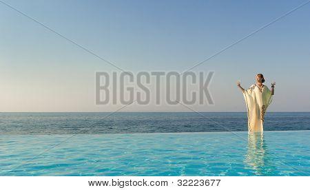 Woman In Long Dress Like Greek Goddess Posing Near Edge Of Infinity Pool On A Beach