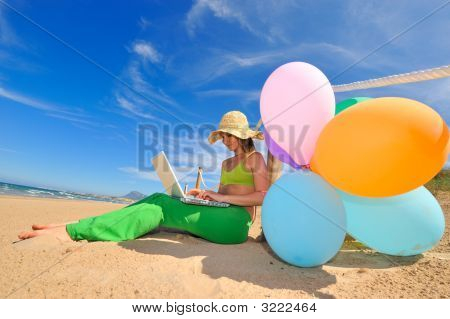 Girl With Colorful Balloons Using A Laptop
