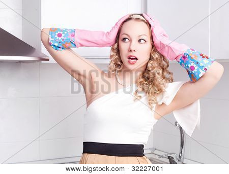 beautiful surprised young housewife wearing rubber gloves in the kitchen at home