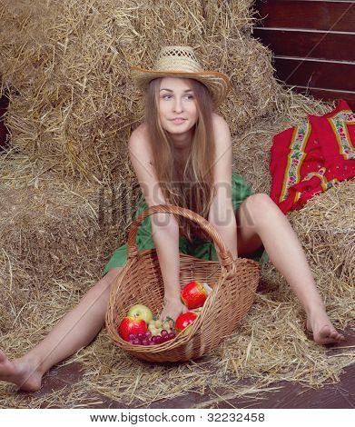 beautiful blonde country girl posing on yellow hay