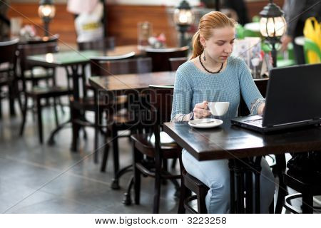 Girl With Computer In Cafe