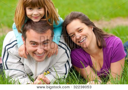 Young happy family having fun in the grass on beautiful spring day