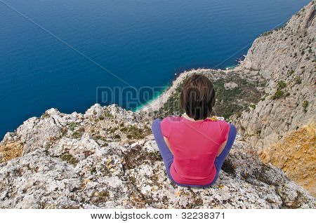 Girl  sitting  on precipice above sea