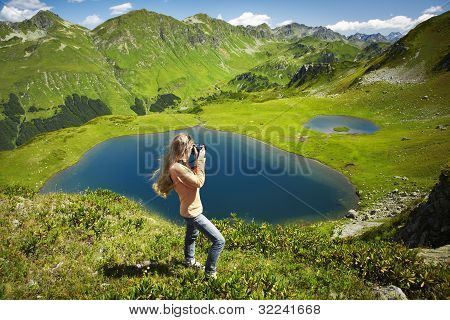 Beautiful Young Woman With Red Hair Standing On Rock, And Photographs