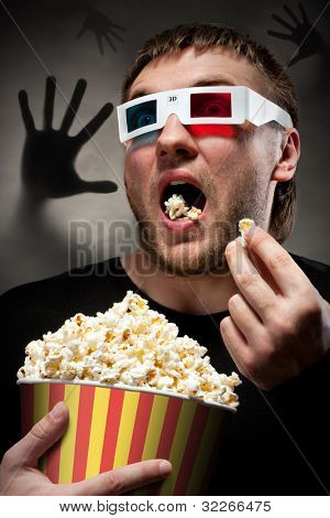 Portrait of scared man watching 3D movie and eating popcorn with dark hand behind