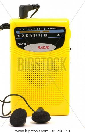 Yellow retro radio with earphones on white background