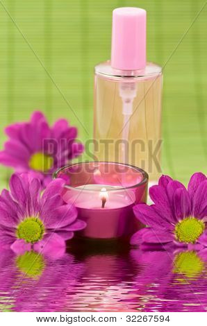 Wellness scene with fragrance bottle, candle and flowers on green bamboo with water reflection