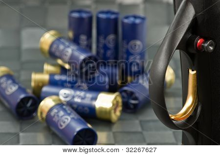 Close up on shotgun trigger and ammunition in background