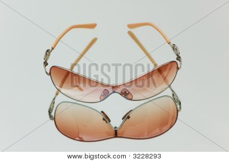 Stylish Sun Glasses On Highly Reflective Background