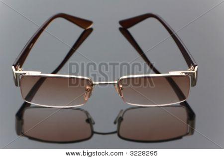 Stylish Sun Glasses On Highly Reflective Background