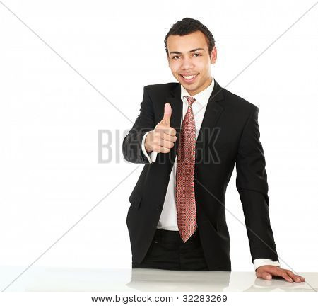 A young man standing near desk and showing ok, isolated on white background