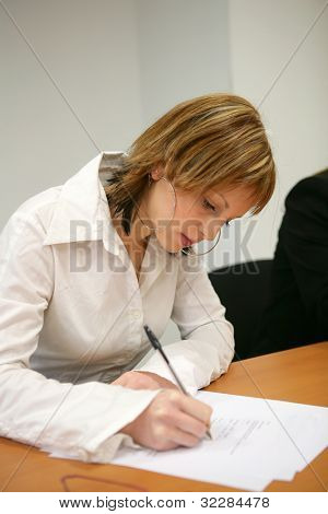 Blond office worker writing