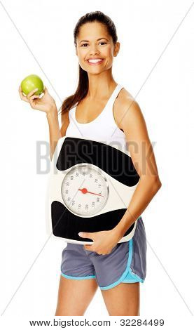 portrait of a slim fitness woman with apple and scale promoting healthy weightloss