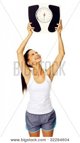 portrait of a cheerful hispanic woman who is happy with her weight and holds scale above her head