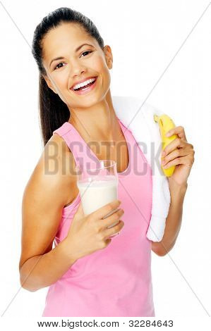 portrait of a healthy hispanic woman with banana smoothie protein shake after gym session