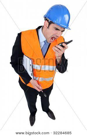 Engineer shouting into a two-way radio