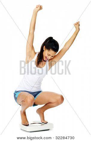 Retrato de una mujer hispana emocionada en una escala que ha perdido peso y está en forma y saludable