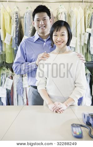 Asian male and female drycleaners smiling