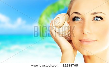 Beautiful woman enjoying beach, closeup female face portrait, happy girl holding seashell, relaxing in nature, summer travel vacation and spa relaxation concept