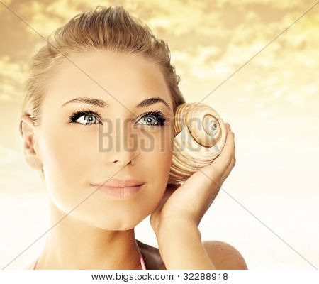 Beautiful woman face over beach sunset, lovely lady portrait with seashell, female enjoying nature sounds, sexy girl outdoor over sky, summer vacation and spa relaxation